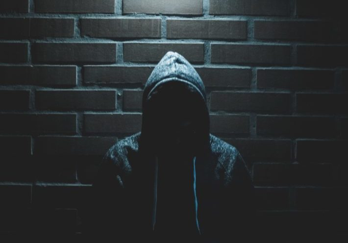 Man in a dark hood against a brick wall with a light above him